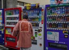 一个在贩卖机的人买的饮料 免版税库存图片