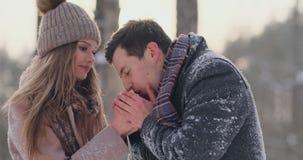 一个有同情心的人在街道上的冬天温暖他的妻子` s手在一个积雪的公园 股票录像