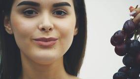 一个美丽的亭亭玉立的女孩吃健康果子 举行成熟葡萄花束和真相的一俏丽的年轻女人的画象 股票视频
