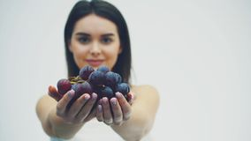 一个美丽的亭亭玉立的女孩吃健康果子 在此期间,一俏丽的年轻女人在她的手上起来成熟葡萄花束  股票视频