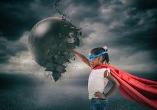 一个特级英雄孩子的力量和决心反对一个击毁的球的 免版税图库摄影