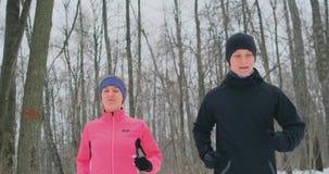 一个男人和一名妇女一件桃红色夹克的在跑通过公园的冬天慢动作的 健康生活方式 股票视频