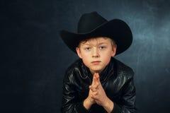 一个男孩模型的画象在皮夹克和帽子的 图库摄影