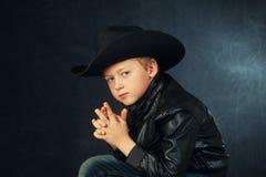 一个男孩模型的画象在皮夹克和帽子的 免版税库存照片