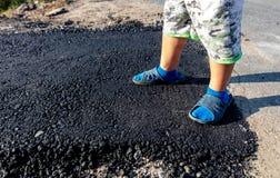 一个男孩的脚一条新的柏油路的 免版税库存图片