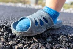 一个男孩的脚一条新的柏油路的 图库摄影