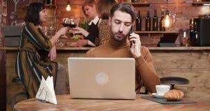 一个英俊的年轻商人谈话在他的电话,当工作在酒吧时 影视素材