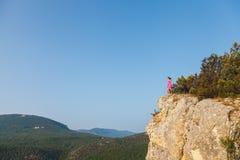 一件桃红色礼服的一个女孩在悬崖前面的一个岩石站立 免版税库存图片