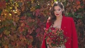 一件礼服和一件红色外套的女孩有一花束的在秋天公园 影视素材
