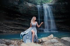 一件豪华蓝色礼服的一个卷曲白肤金发的女孩坐白色石头反对一个美妙的风景的背景 河 免版税库存图片