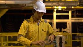 一件黄色工作制服的年轻人、玻璃和盔甲在产业环境里,石油平台或者液化气植物 股票视频