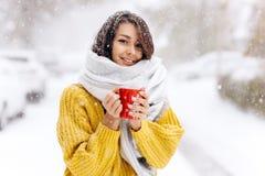 一件黄色毛线衣、牛仔裤和一个白色围巾身分的微笑的深色头发的女孩与在一条多雪的街道上的一个红色杯子在a 库存图片