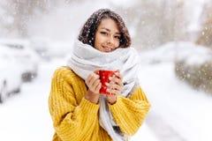 一件黄色毛线衣、牛仔裤和一个白色围巾身分的微笑的深色头发的女孩与在一条多雪的街道上的一个红色杯子在a 免版税库存图片