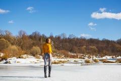 一件黄色毛线衣的一个女孩有短的理发的在河的冰站立  免版税库存图片