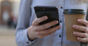 一份衬衣固定的单元电话和咖啡的年轻女商人在她的手和发短信上,特写镜头视图 股票视频