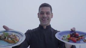 一位微笑的有胡子的厨师的接近的画象黑一致的demostriruet两板材可口盘身分的在a 股票视频