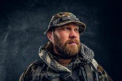 一位残酷有胡子的战士的特写镜头画象军用被伪装的制服的,看斜向一边 库存图片
