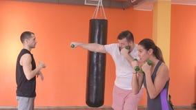 一位白种人男性教练员在武道,自卫,健身房,慢动作方面教一个有胡子的人和女孩正确的拳打 影视素材