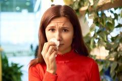 一俏丽的少女按一块餐巾对她的鼻子 她遭受过敏和鼻涕 免版税库存图片