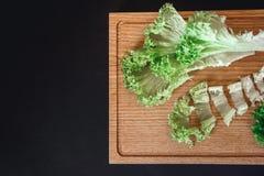一半在老棕色木桌上的新鲜的圆白菜在与拷贝空间的黑背景 顶视图 免版税库存照片