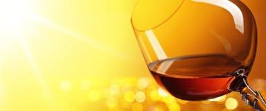 一口威士忌酒在黄色背景的白兰地酒 库存图片