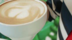一只女性手采取一个杯子在桌上的热奶咖啡并且给她的嘴唇带来它 股票录像