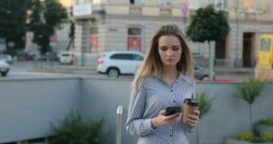 一可爱的少女在街道上走用一个咖啡和电话在她的手上,当键入时 股票录像
