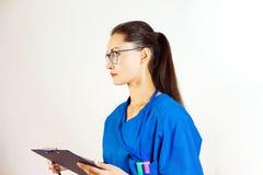 一名女性医护人员在她的手上拿着一个文件夹,并且神色到左边,她是戴着眼镜和一件蓝色制服 空白 免版税库存照片