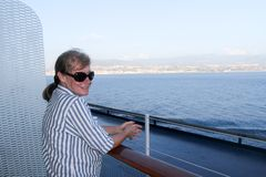 一名资深妇女享受从巡航通过墨西拿海峡的船的看法,意大利 图库摄影