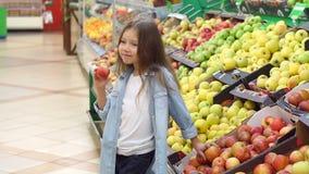 一女孩的画象在有苹果计算机的一个超级市场在她的手上 股票视频