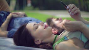 一对年轻夫妇在公园变冷 图库摄影