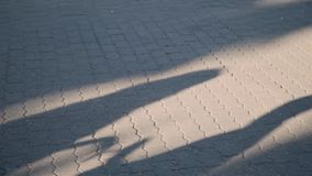 一对年轻夫妇的晚上阴影在爱的在路面 两个人剪影在阳光下 男性和女性走 影视素材