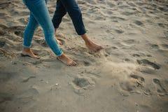 一对年轻夫妇获得乐趣并且走在海海岸线 腿关闭  在海滩的浪漫日期 免版税库存照片