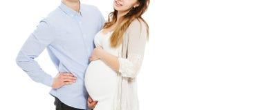 一对年轻怀孕的夫妇的播种的画象在被隔绝的白色背景的 免版税库存图片
