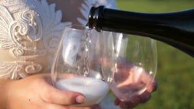 一对爱恋的夫妇的配合 庆祝成功和胜利 从一个瓶的倾吐的汽酒到透明酒里 股票录像