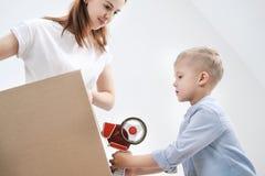 一年轻女人和儿童棍子纸板箱有分配器和橡皮膏的 库存照片