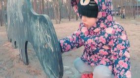 一点一件五颜六色的桃红色夹克的逗人喜爱的女孩画与在黑板的白垩以在的恐龙的形式孩子的 股票录像