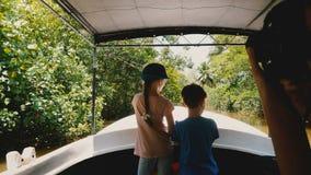 一点愉快的女孩和男孩一起在徒步旅行队游览沿异乎寻常的密林河,年轻女人的小船风帆拍照片他们 股票视频