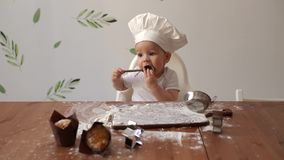 一点鲜美厨师的盖帽的逗人喜爱的男孩在厨房里舔一把木匙子用面粉 影视素材