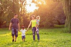 一起享用在公园的愉快的童年年轻家庭 库存图片