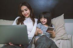 一起使用智能手机和膝上型计算机的母亲和女儿在卧室 概念查出的技术白色 免版税库存图片