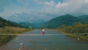 一起年轻夫妇在河的桥梁 夏天多云天气 从空气的射击 股票录像