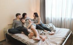一起放松在BedÑŽ幸福家庭概念的家庭 库存图片