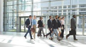 一起走在大厅办公室的小组不同的商人 免版税库存照片