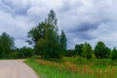 乡下公路在一个领域的郊区在村庄 照片在拉脱维亚被拍了 免版税库存照片