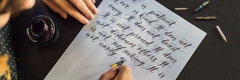 书法家手在白皮书写词组 关于题写装饰装饰的信件的爱的圣经词组 免版税库存照片