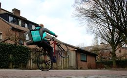 乌得勒支,荷兰,2019年2月19日:做wheely,当食用食物在袋子时的deliveroo工作者 免版税库存照片