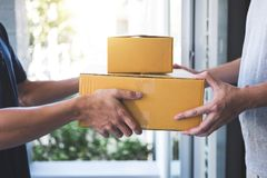 交付给小包箱子的邮件人接收者,年轻所有者接受从岗位发货,家的纸板箱包裹 免版税图库摄影