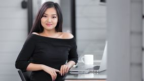 享受断裂的时兴的年轻亚裔女实业家画象坐在看照相机的桌上 股票视频