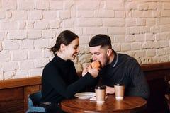 享用在咖啡馆的愉快的爱恋的夫妇早餐 免版税库存照片
